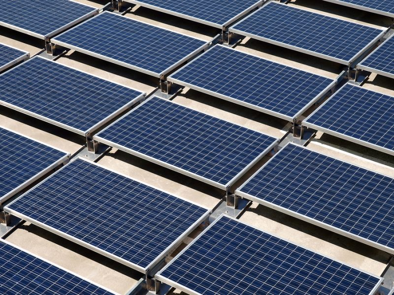 Photovoltaic solar panels on a concrete rooftop.